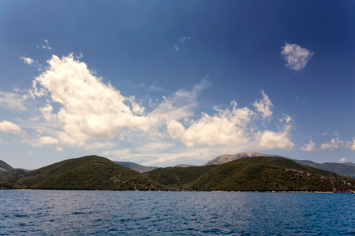 Puffy clouds above the island of Meganisi in Greece
